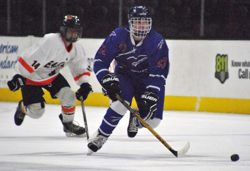 . Jon Behm - The Morning Journal<br> Bay\'s Will Kenny gives chase to a loose puck as North Olmsted\'s Ryan Godin works to catch up during the first period on Dec. 22 at The Q.