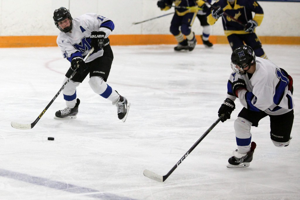 . Randy Meyers - The Morning Journal<br> Midview\'s Nicholas Verlotti slaps the puck to Jonathan Rodgers on the open ice against Olmsted Falls during a Southwestern Conference tournament semifinal on Jan. 15.