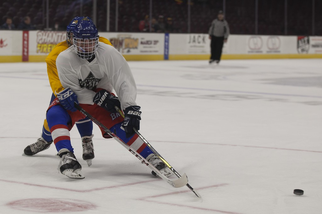 . Jen Forbus - The Morning Journal<br> Bay\'s Will Kenney keeps himself between the puck and Sam Cameratta of Notre Dame Cathedral Latin in the Championship round of the  GCHSHL All-Star Hockey game at the Quicken Loans Area on Sunday.