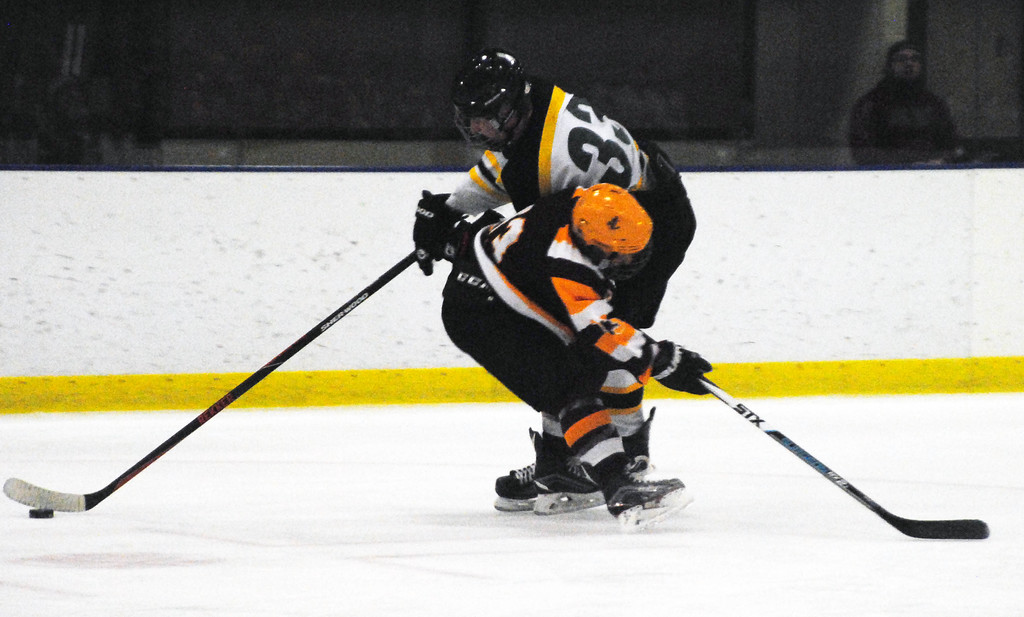 . Jon Behm - The Morning Journal<br> Avon Lake\'s Isaac Young collides with Amherst\'s Tyler Waldecki during the first period of a Brooklyn District first round game on Feb. 13 at Brooklyn\'s John M. Coyne Recreation Center.