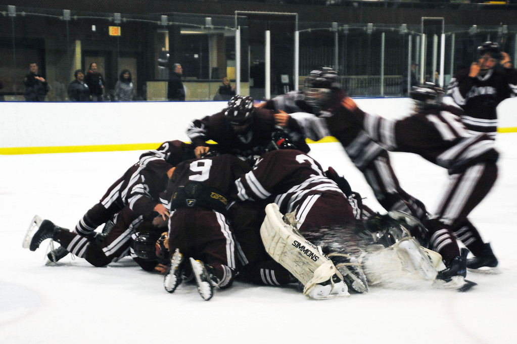 . Jon Behm - The Morning Journal<br> Rocky River players pile on top of each other after claiming the Baron Cup I title with a 2-1 win over Shaker Heights on Feb. 11 at Brooklyn\'s John M. Coyne Recreation Center.