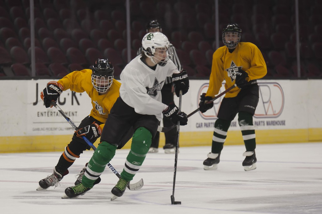. Jen Forbus - The Morning Journal<br> Elyria Catholic\'s Ryan Sustersic turns the puck toward the White goal in the Championship round of the GCHSHL All-Star Hockey game at the Quicken Loans Area on Sunday.