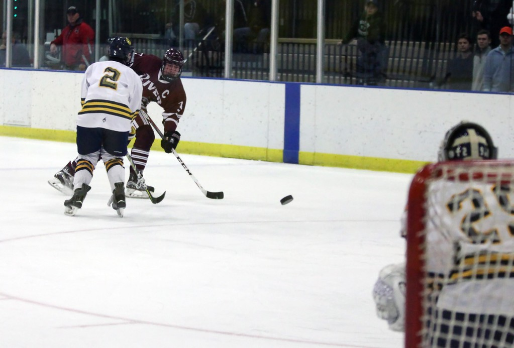 . Randy Meyers - The Morning Journal<br> Ted Stueber of Rocky River takes a long shot on goal past Santino Pignatiello of St. Ignatius during the second period on Feb. 24.