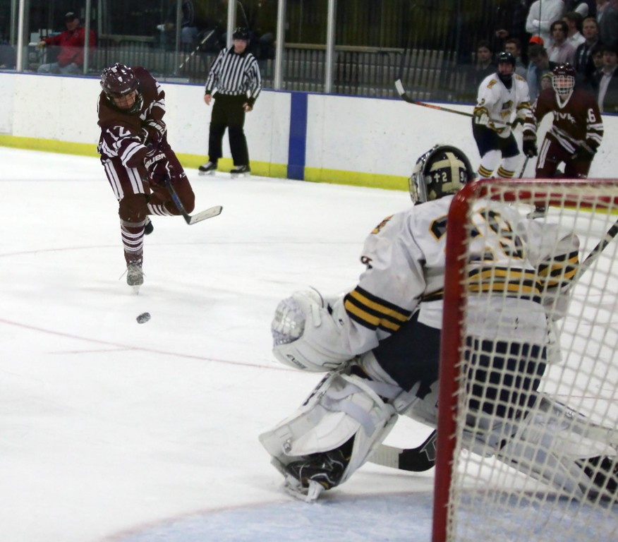 . Randy Meyers - The Morning Journal<br> Spencer Asmar of Rocky River takes a shot on goal as St. Ignatius goalee Ben Savarino defends during the second period on Feb. 24.