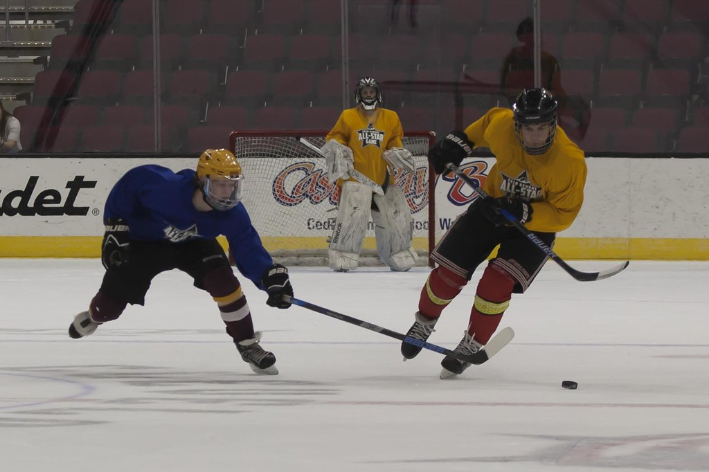 . Jen Forbus - The Morning Journal<br> Jared Aslaksen of Avon Lake tries to take possession of the puck from Will Morgan of Brecksville in the second round of the GCHSHL All-Star Hockey game at the Quicken Loans Area on Sunday.