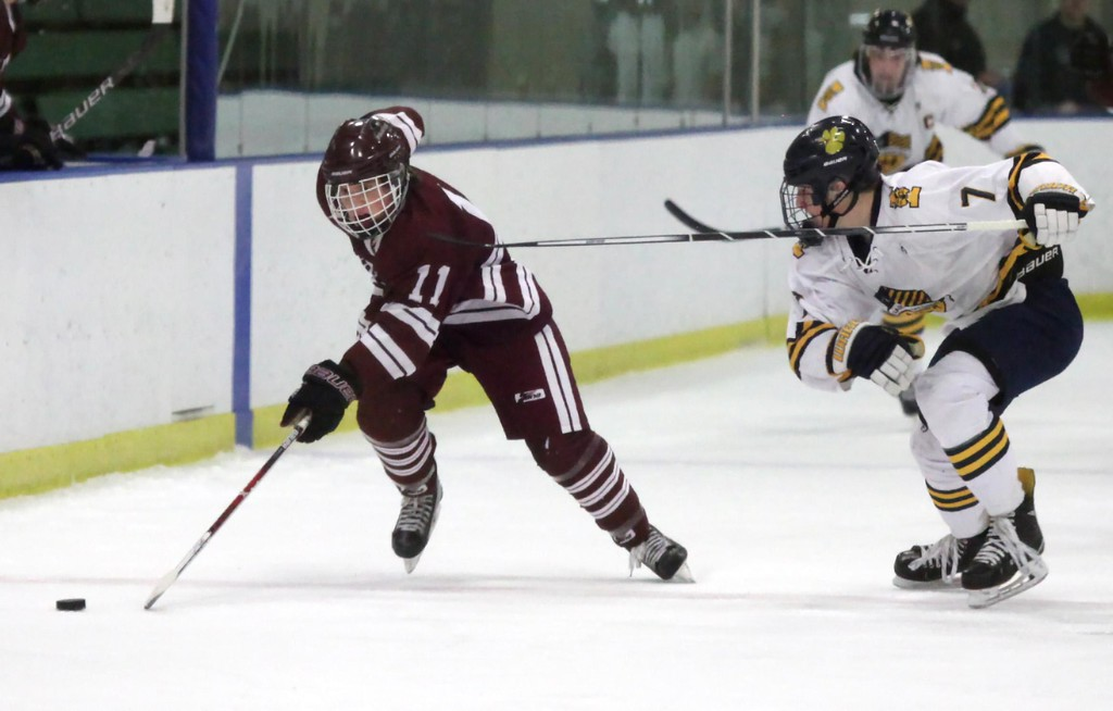 . Randy Meyers - The Morning Journal<br> Nolan Weaver of Rocky River moves the puck by Greg Langermeier of St. Ignatius on Feb. 24.