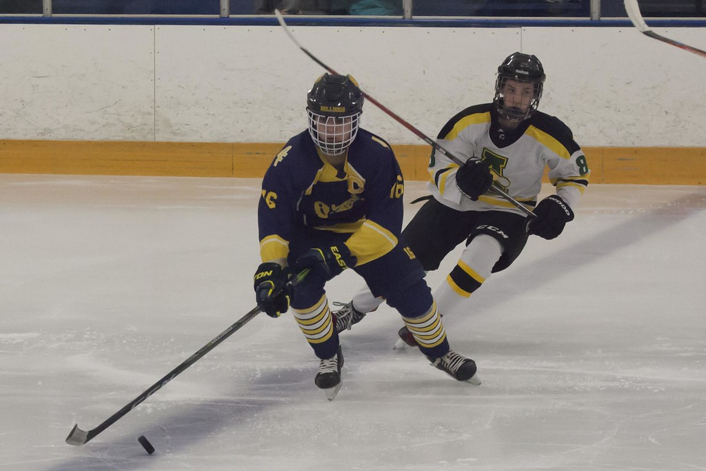 . Jen Forbus - The Morning Journal<br> Jacob Kerkay of Olmsted Falls controls the puck as Amherst\'s Nathan Harmych moves in.