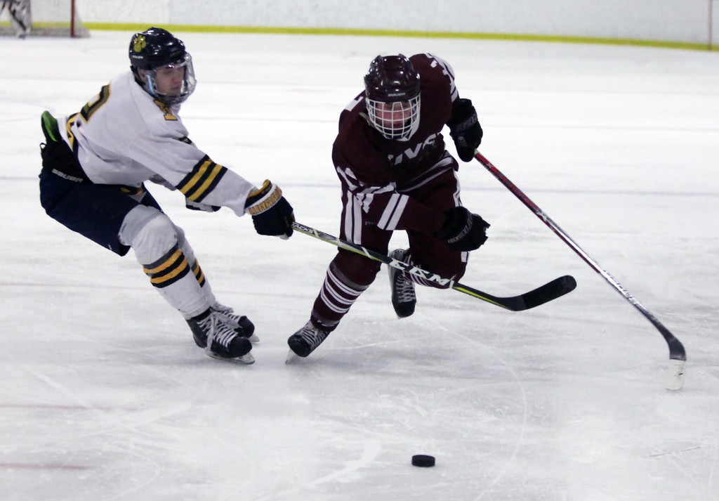. Randy Meyers - The Morning Journal<br> Santino Pignatiello of St. Ignatius tries to check Nolan Weaver of Rocky River from the loose puck during the second period on Feb. 24.