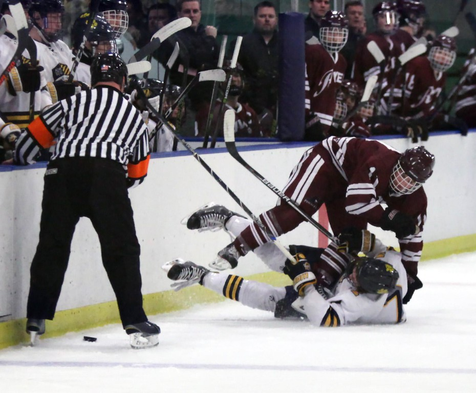 . Randy Meyers - The Morning Journal<br> Rocky River\'s Nolan Weaver collides with Greg Langermeier of St. Ignatius at the wall during the first period of the district semifinal on Feb. 24.