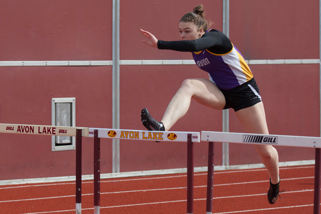 . Jen Forbus - The Morning Journal<br> Avon\'s Kamryn Sharer easily clears the hurdle in the 100 meter hurdle event at the Avon Lake Invitational on March 31.