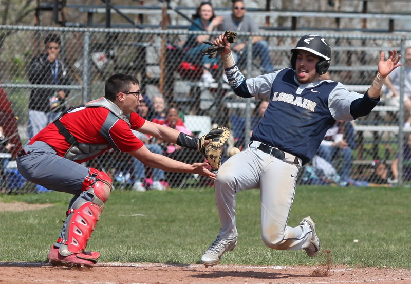 Randy Meyers - The Morning Journal<br /> Lorain's Ray Rodriguez slides into home safely as the throw is late to Elyria's Michael Bennetto during the second game of a doubleheader on April 15.