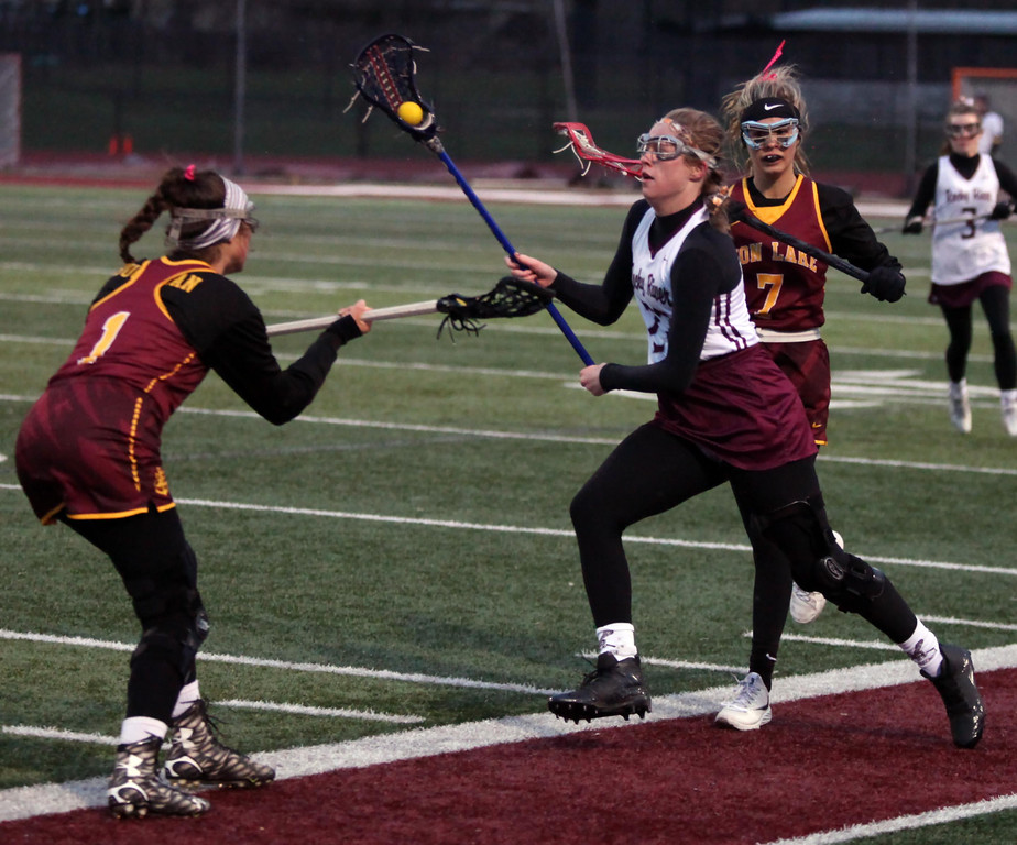 . Randy Meyers - The Morning Journal Bridget McCue of Rocky River runs  through the defense by Liv MacDonald and Macey Buchanan of Avon Lake on  Monday