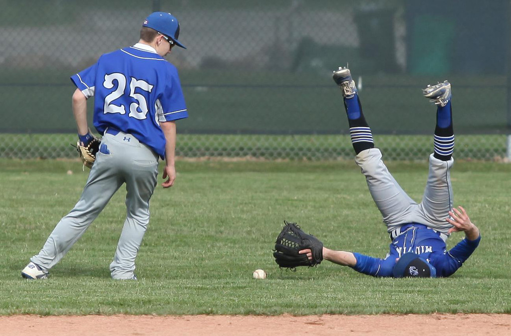 . Randy Meyers - The Morning Journal Midview right fielder Seth Sanders  flips as he dives for a fly ball against Amherst while teamate Connor  Bansek looks on during Monday afternoon