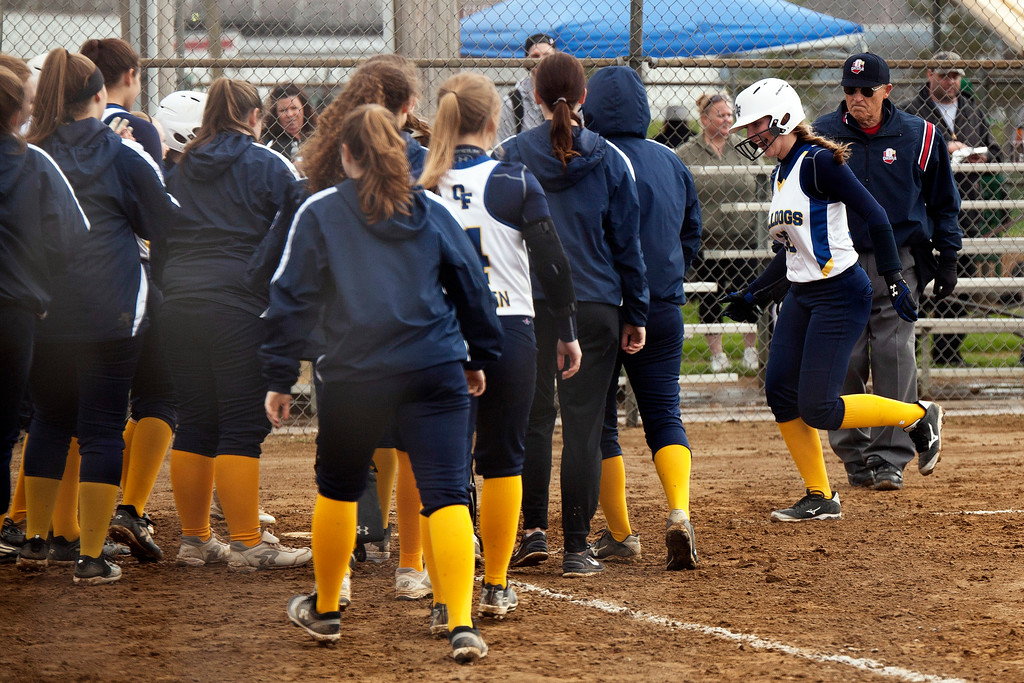 . Jen Forbus - The Morning Journal<br> Danielle Stevens (right) is greeted by her fellow Bulldogs as she crosses the plate on a three-run homerun against the Wellington Dukes on April 27 at the Prebis Memorial Classic at Wellington Community Park.