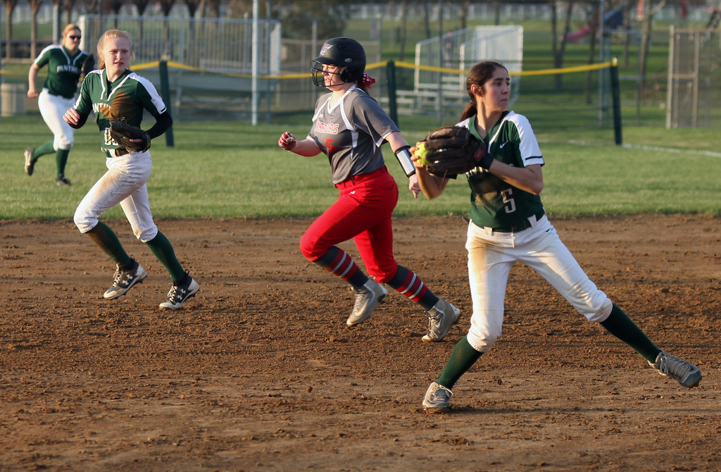 . Randy Meyers - The Morning Journal<br> Elyria Catholic infielder Stephanie Griffin fields a ground ball and throws to home against Fairview during the Prebis Memorial Classic at Wellington Community Park on April 27.