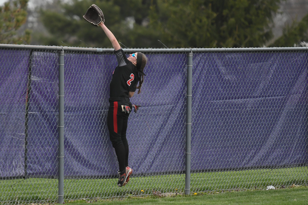 . Eric Bonzar�The Morning Journal<br> Elyria\'s Macy Taylor tries to pull back a solo home run hit by Oak Harbor\'s Ashley Riley at LaGrange Community Park during the Prebis Memorial Classic on April 27.