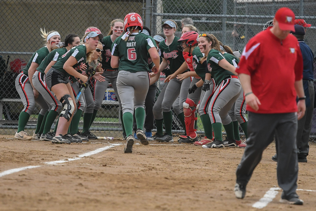 . Eric Bonzar�The Morning Journal Oak Harbor\'s Ashley Riley is mobbed at home plate by her teammates after hitting a solo home run against Elyria at LaGrange Community Park during the Prebis Memorial Classic on April 27.