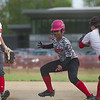 Max Feliciano of Shaker Heights (center) tries to avoid Mentor's first baseman Bernadette Calvey (9) while running the bases during a game at Mentor High School on May 10, 2017.  Mentor defeated Shaker 10-0.