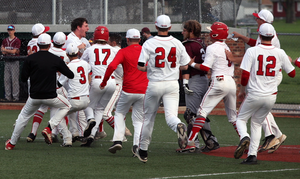 . Randy Meyers - The Morning Journal<br> The entire Firelands baseball team mobs Calvin Stull after he hit the game-winner in the bottom of the eighth inning to beat Rocky River in a Division II Parma District semifinal on May 15.