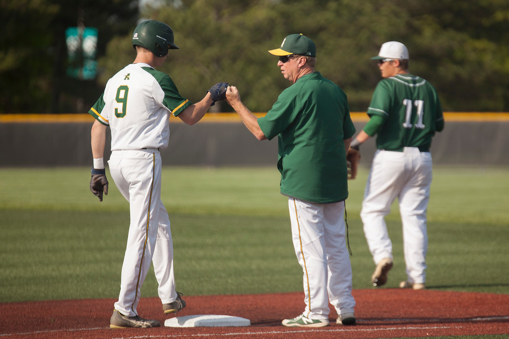 . Jen Forbus - The Morning Journal<br> Amherst assistant coach Dr. David Rositano congratulates Ryan Glowacki at first base against Strongsville on May 24.