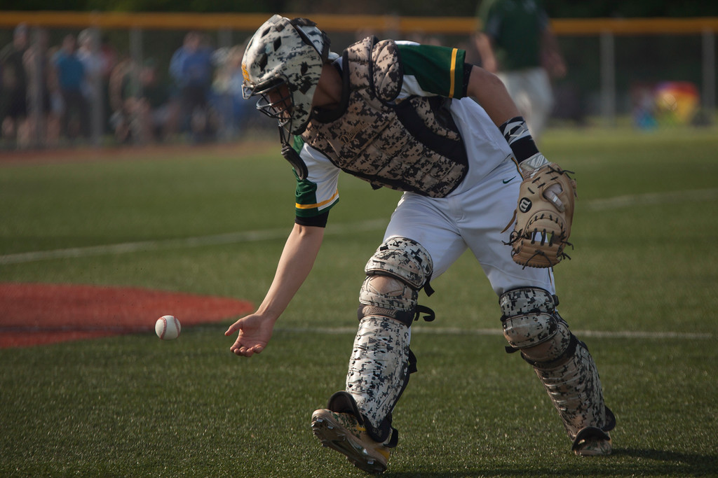 . Jen Forbus - The Morning Journal<br> Amherst catcher Hunter Cassidy barehands a bunt hit foul during the Comets\' game against the Strongsville Mustangs on May 24.