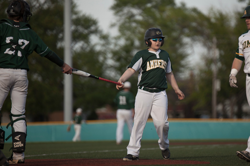 . Jen Forbus - The Morning Journal<br> Amherst\'s batboy stays busy keeping the Comet bats off the field against Strongsville on May 24.