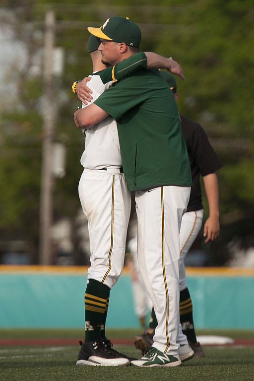 . Jen Forbus - The Morning Journal<br> Assistant coach Mark Coughlin consoles Amherst pitcher Evan Shawver after a tough loss to the Strongsville Mustangs on 24.
