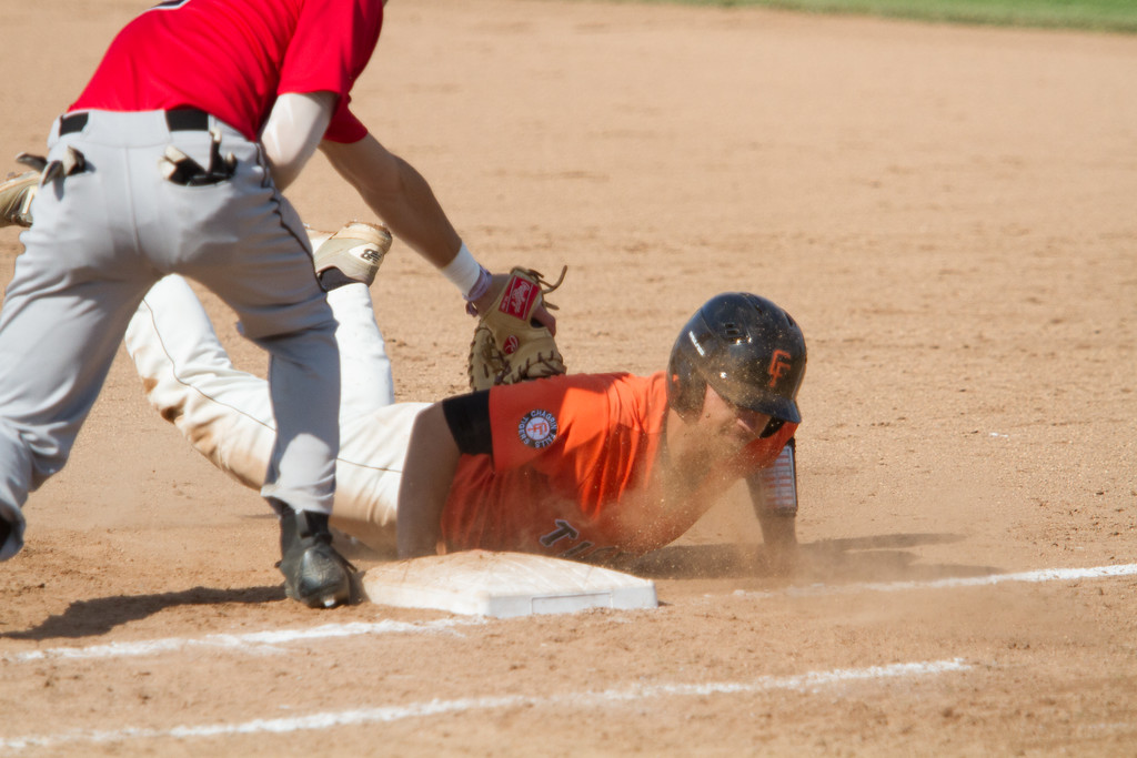 . Michael Johnson - The News-Herald Chagrin Falls\' Cole Newbauer slides back into first base during  the Hudson Regional Semifinal against Canfield on May 26.  Canfield defeated Chagrin Falls 2-0.