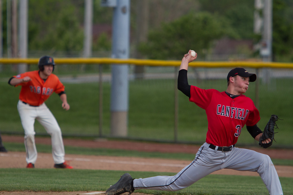 . Michael Johnson - The News-Herald Canfield\'s Jack Rafoth pitches with a man on first base during the Hudson Regional Semifinal on May 26.  Canfield defeated Chagrin Falls 2-0.