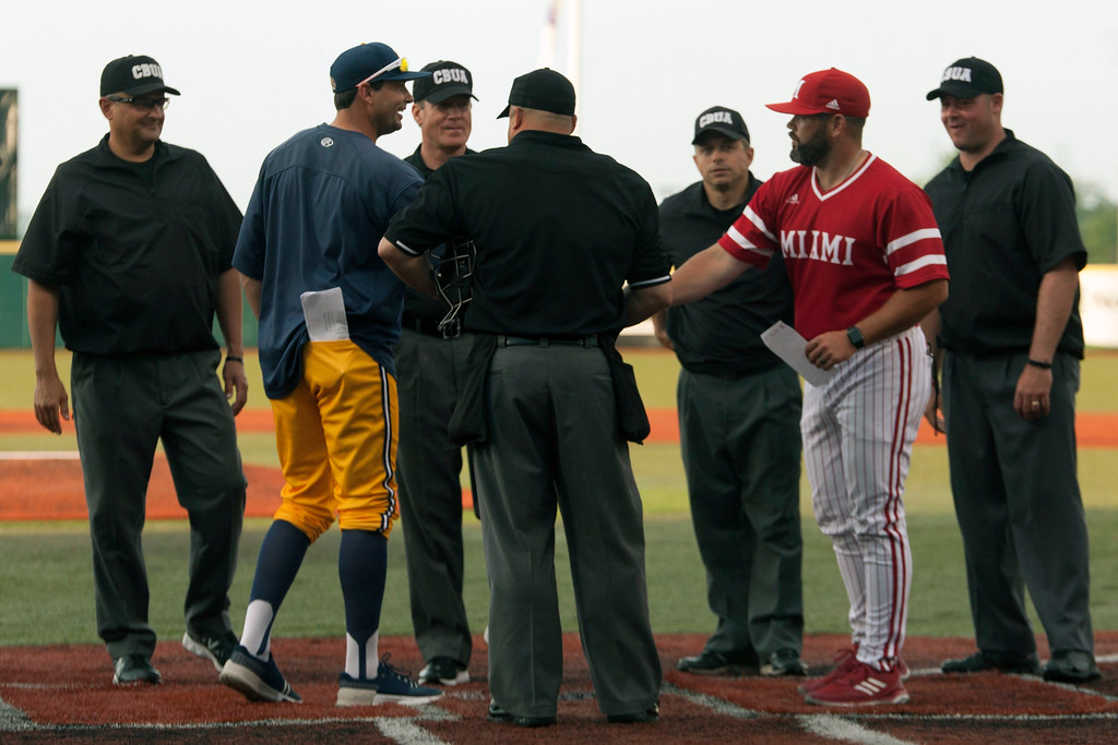 . Jen Forbus - The Morning Journal<br> The coaches for Kent and Miami meet with the umpires prior to the start of the MAC Championship game at Sprenger Stadium on May 26.