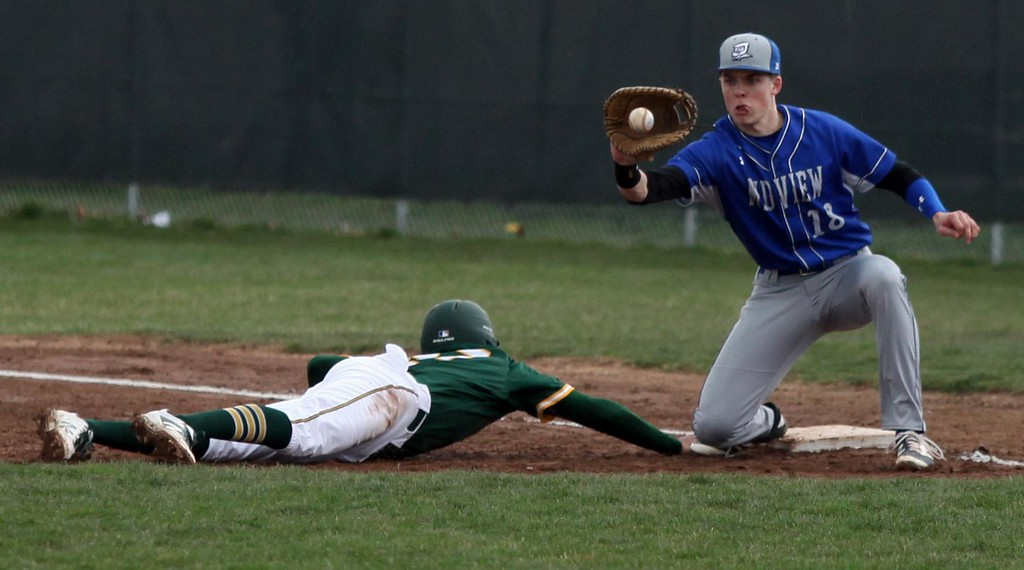 . Randy Meyers - The Morning Journal<br> Midview first baseman Owen Hawke  looks the ball in as Xavier Moore of Amherst dives back to first on April 4.
