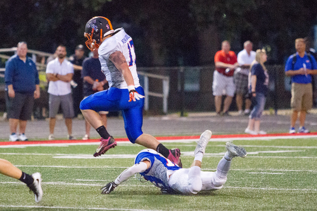 . Barry Booher - The News-Herald Newbury\'s Kade Marker leaps over Blue defender.