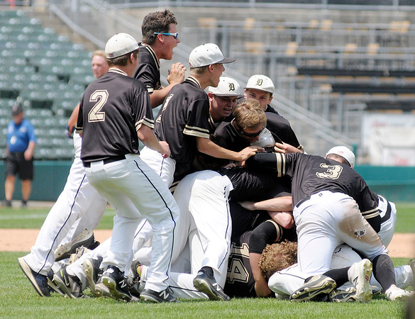 Don Knight | The Herald Bulletin<br /> Peyton Smith's teammates pile on top of him after the Broncos won their second state baseball title in three years on Saturday at Victory Field.