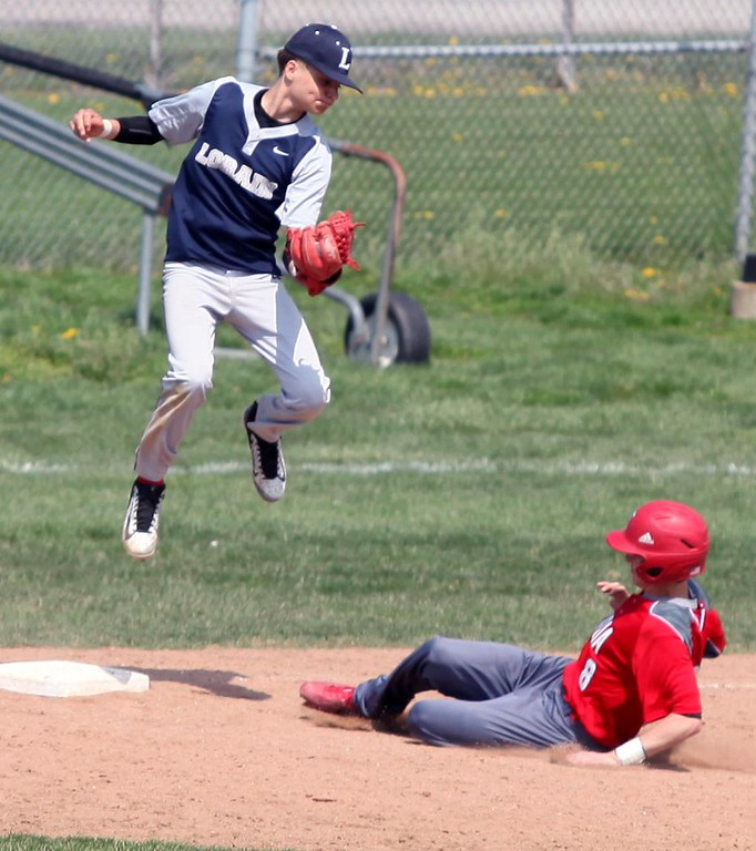 . Randy Meyers - The Morning Journal<br> Lorain third baseman Frank Butcher catches a high throw as Elyria\'s Kevin Reddinger slides into third during the second game of a doubleheader on April 15.