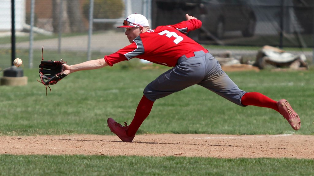 . Randy Meyers - The Morning Journal<br> Elyria\'s third baseman Jordan Reed stretches for the ball against Lorain on April 15.