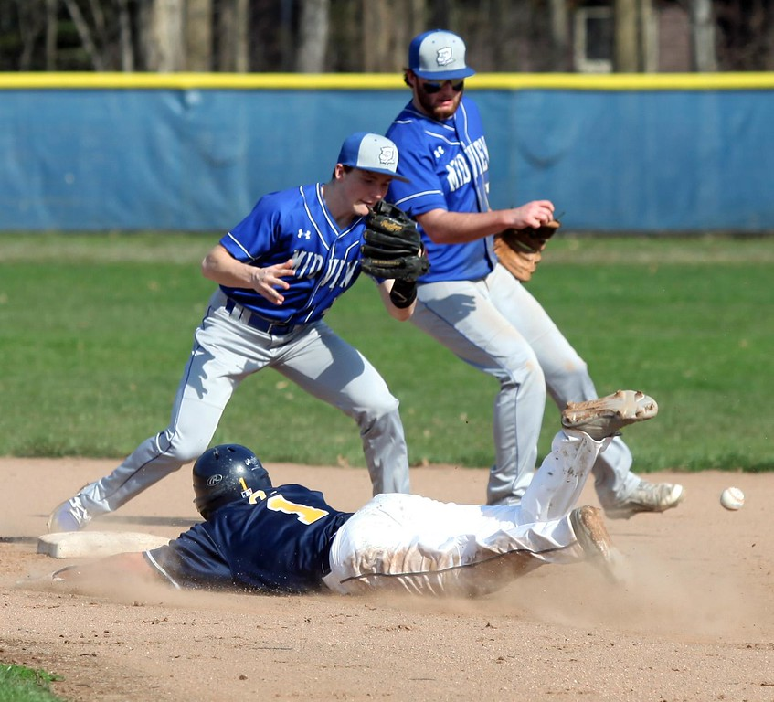 . Randy Meyers - The Morning Journal<br> The ball gets away from Cam Honis of Midview as Ricky Castrigano of Olmsted Falls slides safely into second base on April 10.