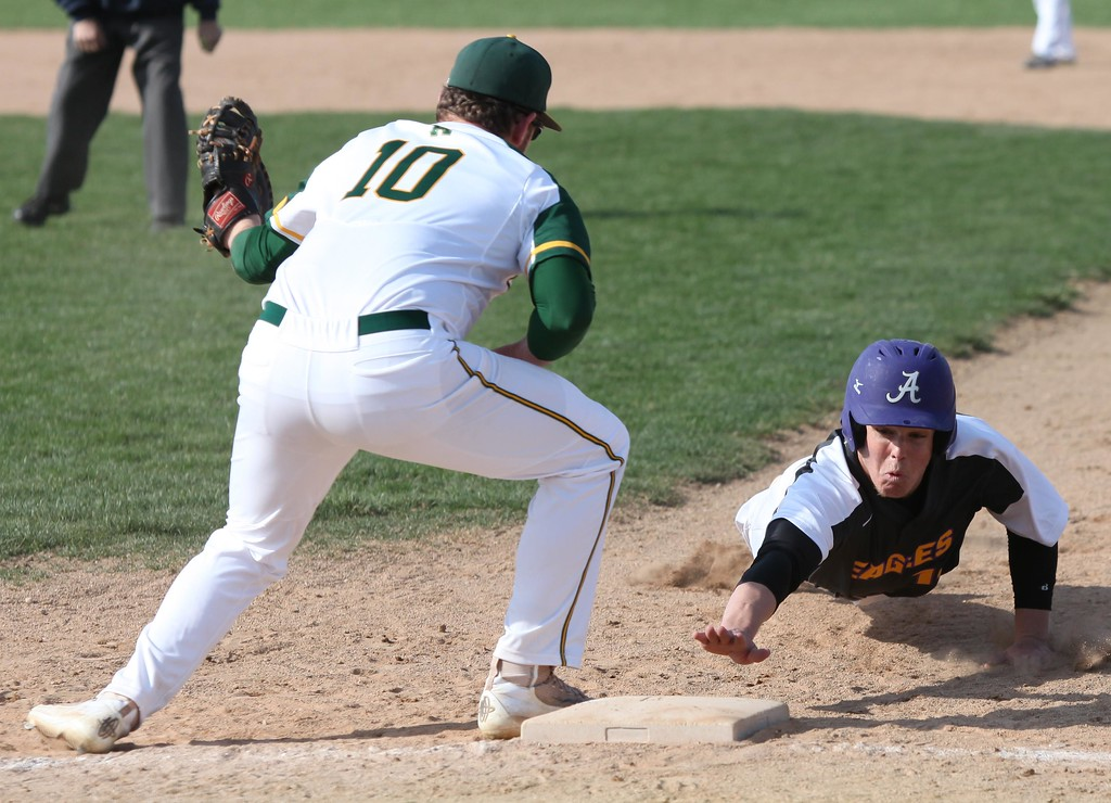 . Randy Meyers - The Morning Journal<br> Logan Doenges of Avon reaches back for first as Amherst first baseman Chad Jones looks to tag on April 12.