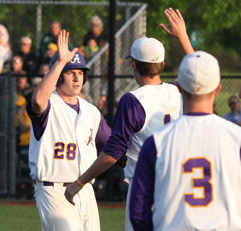 . Randy Meyers - The Morning Journal<br> Avon\'s Taylor Reynolds scores against Medina during the seventh inning and he is congratulated by his teammates on May 26.