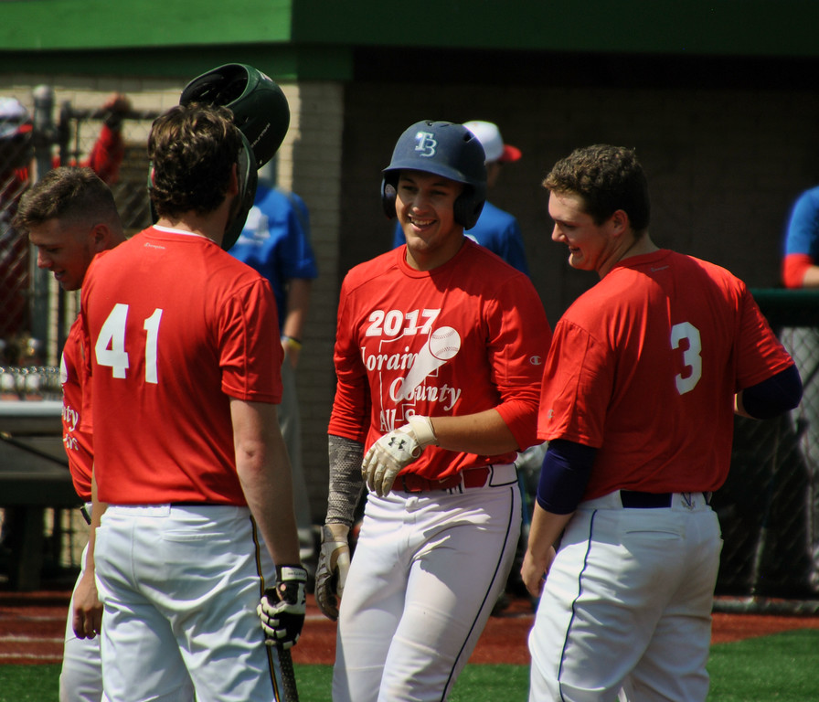 . Jon Behm - The Morning Journal<br> Brookside\'s Tim Ackerman, center, smiles after hitting a grand slam during the Lorain County Senior All-Star Game on May 27 at Oberlin College.