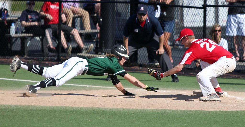 . Randy Meyers - The Morning Journal<br> Jace Drwal of Elyria Catholic is picked off at first base as John Smolik of Lutheran West applies the tag on May 16.