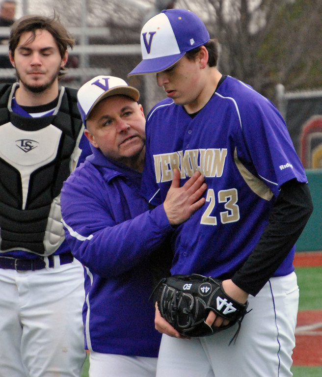 . Jon Behm - The Morning Journal<br> Vermilion coach Jeff Keck congratulates pitcher Evan Ozmun after getting out of a jam during the bottom of the first inning against Elyria Catholic on March 28 at Oberlin College.