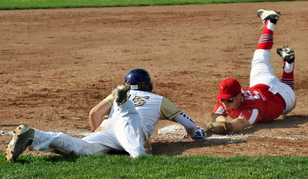 . Jon Behm - The Morning Journal<br> Warren Champion senior Lucas Nasonti dives back to third base ahead of the tag attempt by Lutheran West junior Owen Albers during the bottom of the second inning in a Division III Massillon Region semifinal against Warren Champion on May 26.