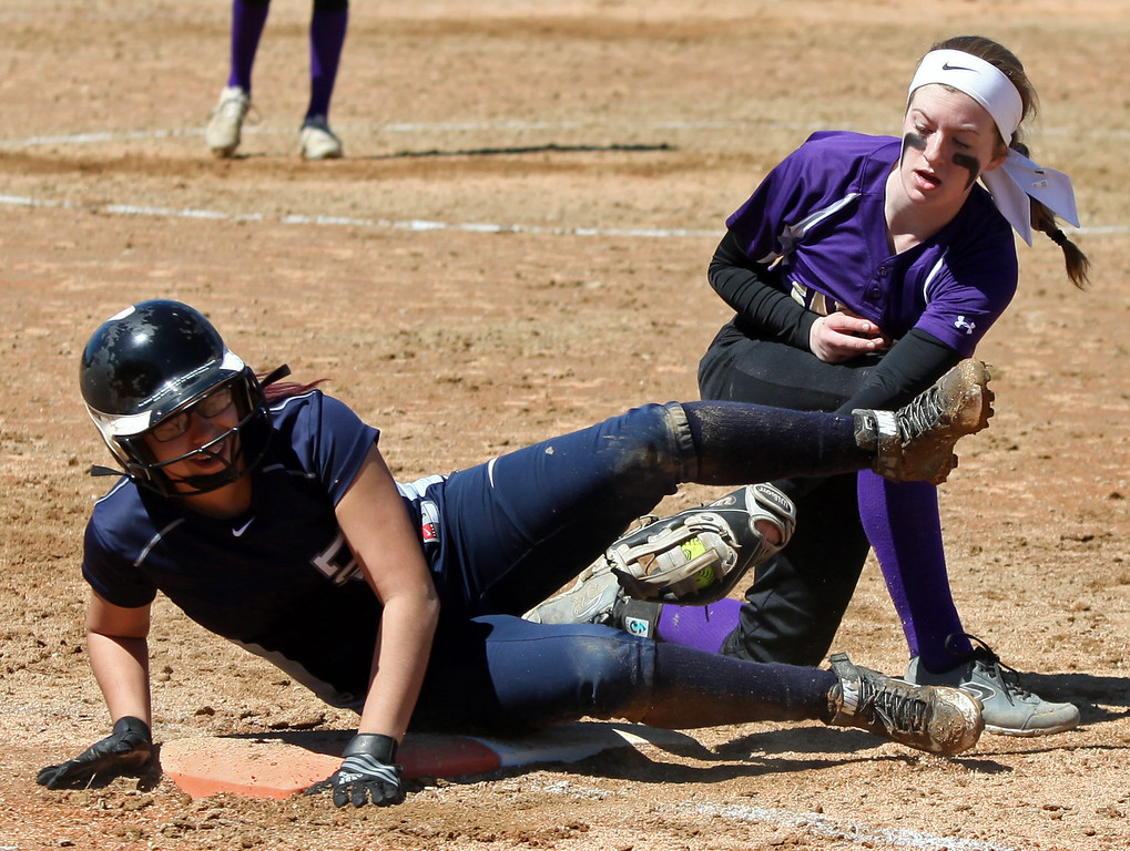 . Randy Meyers - The Morning Journal<br> Lorain\'s Alexis Garcia dives back to first just before the tag by Maria Keller of Vermilion during the first game of a doubleheader on April 8.