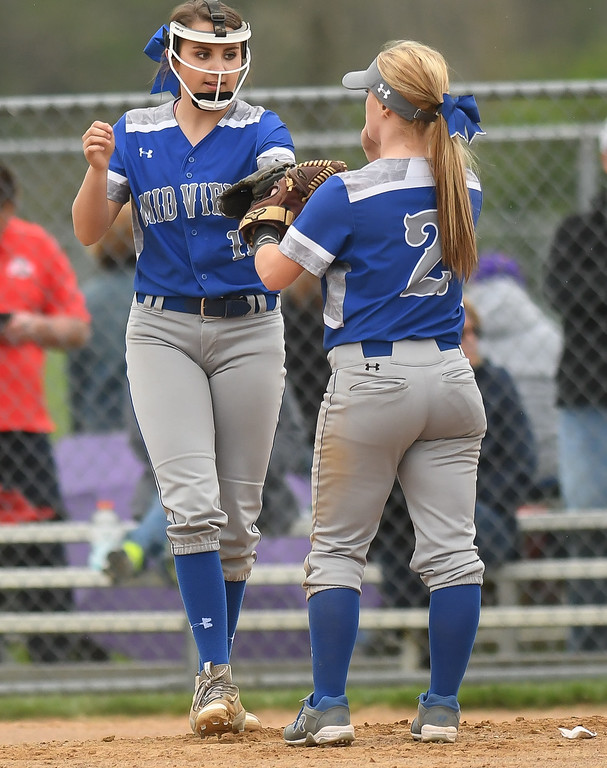. Eric Bonzar�The Morning Journal<br> Midview pitcher Marcella McMahon and Ella Leonard (2) celebrate an out at the pitchers\' mound against Perrysburg, April 28, 2017.
