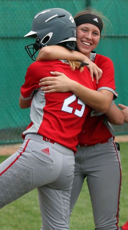 . Randy Meyers - The Morning Journal<br> Elyria\'s April Howser is hugged by teammate Emily Hyer after hitting a home run against Parma on May 24.
