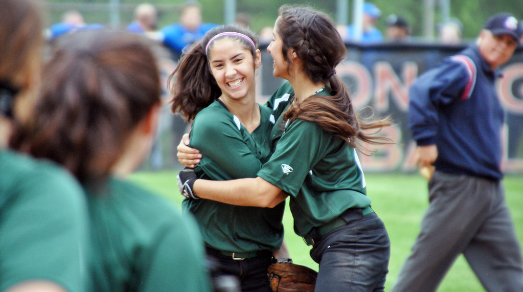 . Jon Behm - The Morning Journal<br> Elyria Catholic freshman center fielder Stephanie Griffin, left, gets a hug from sister Kaylie Griffin after Stephanie made a diving catch to end the top of the eighth inning against Massillon Tuslaw in a Division III Massillon Region semifinal on May 24.