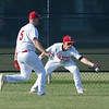Jen Forbus - The Morning Journal<br> Elyria outfielders Chris Willis (5) and Michael Knapp have trouble holding on to the ball on July 25.