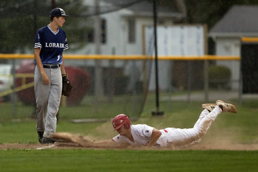 . Jen Forbus - The Morning Journal  Pioneer Chris Willis dives head-first into third base.