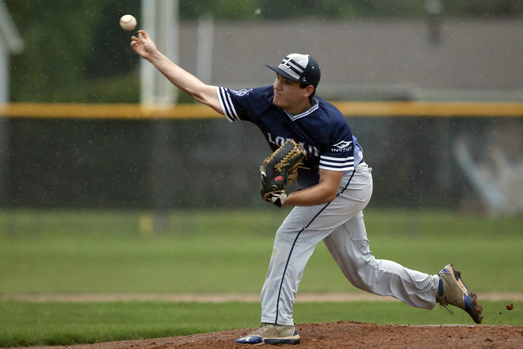 . Jen Forbus - The Morning Journal On the mound for the Titans, Corey Thompson delivers a pitch in the rain.