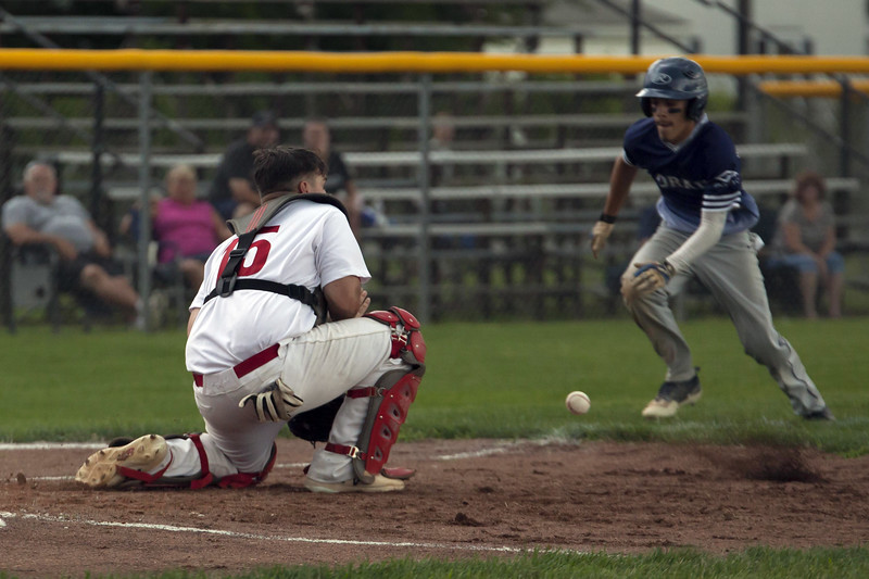 Jen Forbus - The Morning Journal<br />  Lorain's Yandel Ramirez races the throw to Elyria catcher Max Petyon at home plate to score the Titan's lone run of the game.
